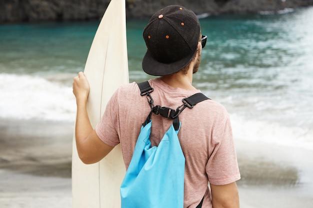 Jovem turista com prancha de pé na beira-mar e olhando para o oceano azul na frente dele