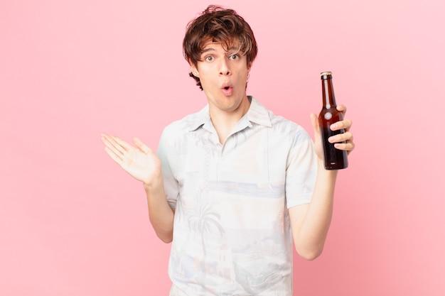 Jovem turista com uma cerveja parecendo surpreso e chocado, de queixo caído segurando um objeto