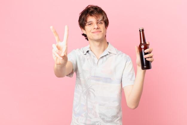 Jovem turista com uma cerveja sorrindo e parecendo amigável mostrando o número dois
