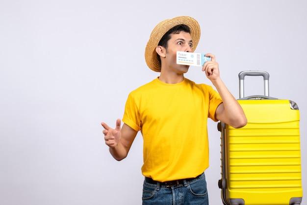 Jovem turista de olhos arregalados em frente a uma mala amarela segurando o ingresso