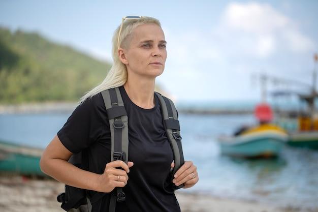 Jovem turista de uma menina loira com mochila na praia com prazer olhando uma linda paisagem do mar, close-up