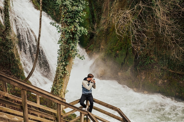 Jovem turista elegante está fotografando a cachoeira.