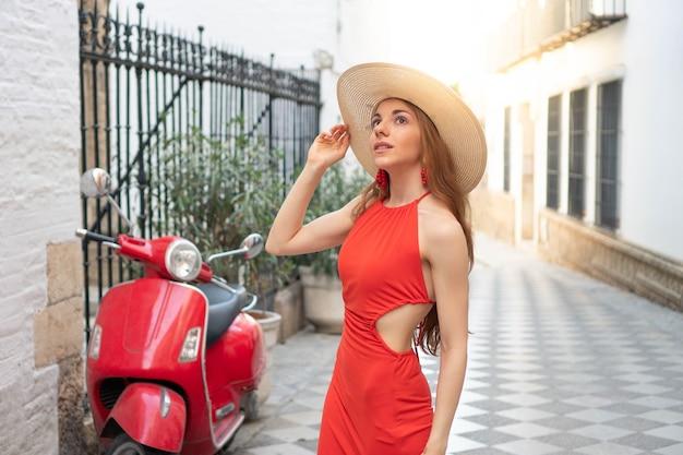Jovem turista elegante visitando uma cidade europeia com um vestido vermelho e uma bicicleta vermelha ao lado