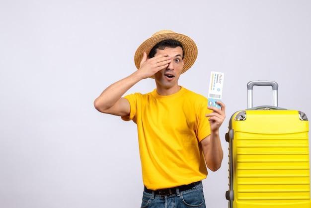 Jovem turista em frente a uma mala amarela, cobrindo os olhos com a mão segurando o ingresso