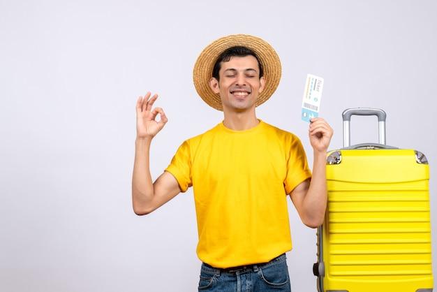 Jovem turista em frente a uma mala amarela, fazendo uma placa de ok segurando o ingresso