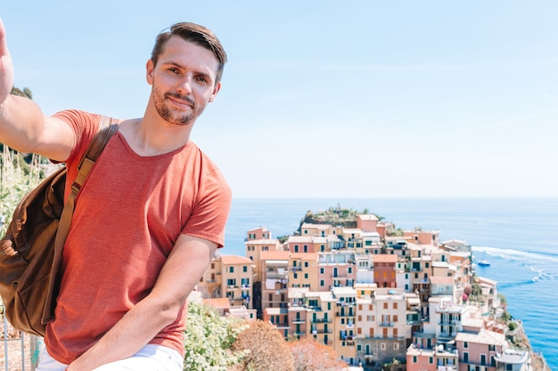 Jovem turista em óculos de sol tomando selfie com vista panorâmica de manarola, cinque terre, liguria, itália