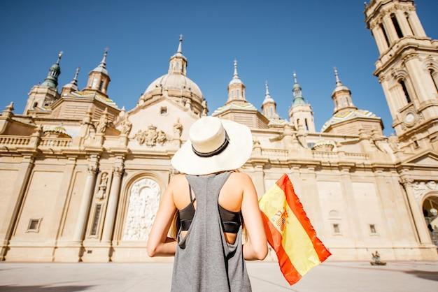 Jovem turista em pé com a bandeira espanhola em frente à famosa catedral na praça central durante o tempo ensolarado na cidade de saragoça, espanha