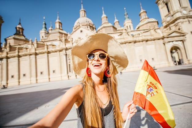 Jovem turista em pé com a bandeira espanhola em frente à famosa catedral na praça central durante o tempo ensolarado na cidade de zaragoza, espanha