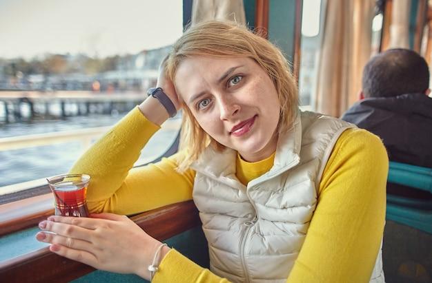 Jovem turista em um barco turístico se senta perto da janela na cabine de passageiros com um copo de chá turco na mão.