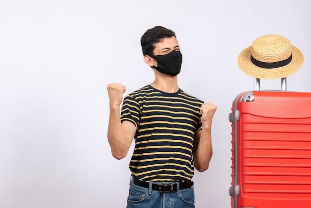 Jovem turista feliz com máscara preta em pé perto da mala vermelha