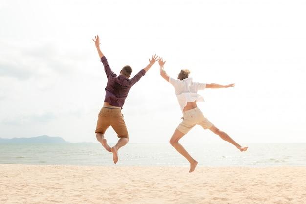 Jovem turista feliz energético homens pulando na praia