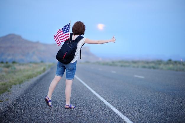 Jovem turista feminina com bandeira americana em mochila pedindo carona ao longo de uma estrada deserta