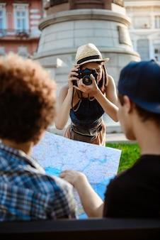 Jovem turista feminina linda tirando foto de seus amigos.