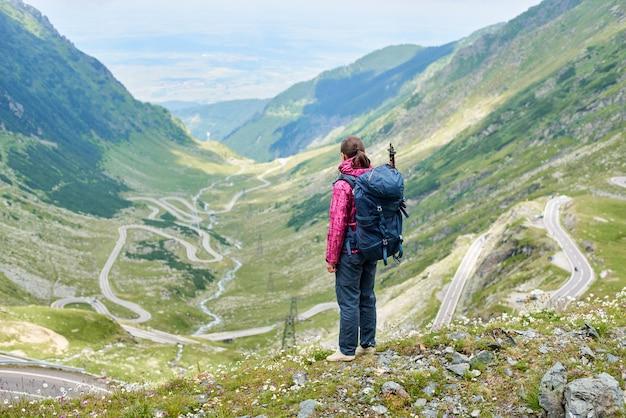 Jovem turista feminina olhando para sinuosa estrada transfagarshan entre encostas rochosas verdes e montanhas na romênia