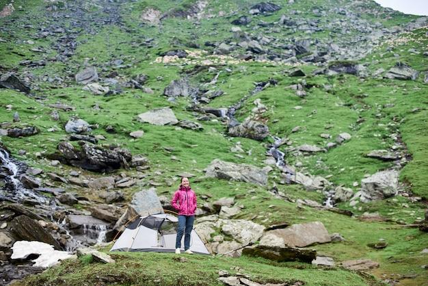 Jovem turista feminina sorridente em pé perto da barraca no prado rochoso verde nas montanhas na romênia
