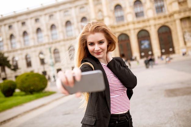 Jovem turista feminina tomando selfie com foto móvel na rua, no centro de viena, áustria