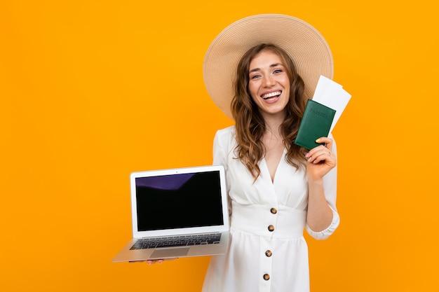 Jovem turista mantém o passaporte na mão e olha bilhetes em um laptop sobre amarelo