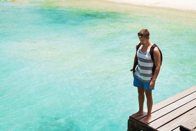 Jovem turista olhando para a água potável e desfrutando de paz