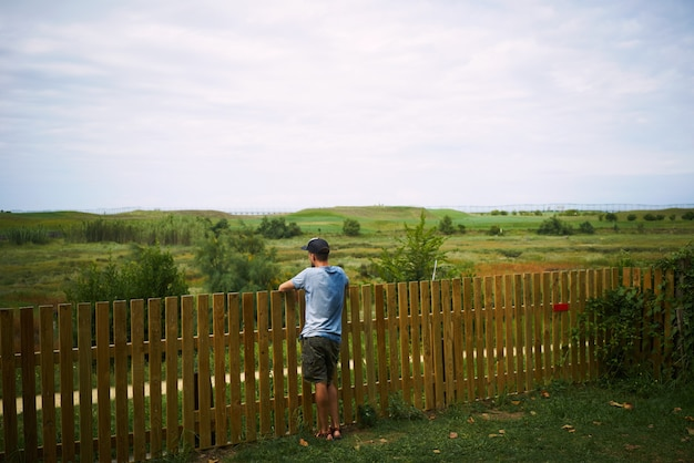 Jovem turista olhando para uma paisagem verde em pé de uma cerca