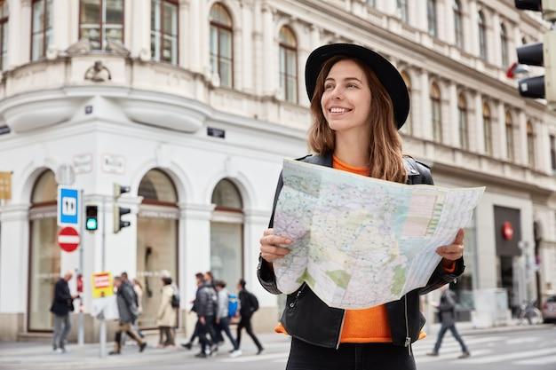 Jovem turista positiva segurando um mapa em papel de viagem e lendo a rota da viagem