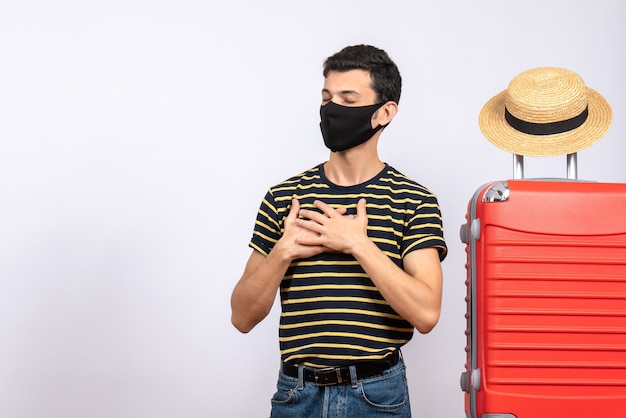 Jovem turista satisfeito de frente com máscara preta em pé perto da mala vermelha