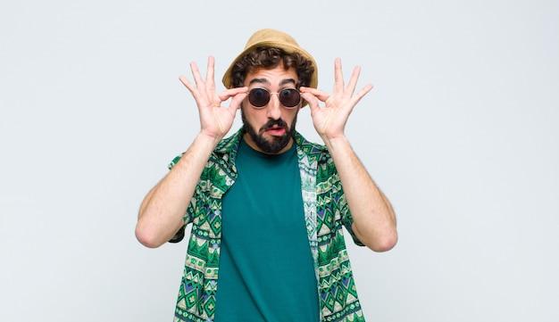 Jovem turista se sentindo chocado, surpreso e surpreso, segurando os óculos com um olhar surpreso e descrente na parede branca