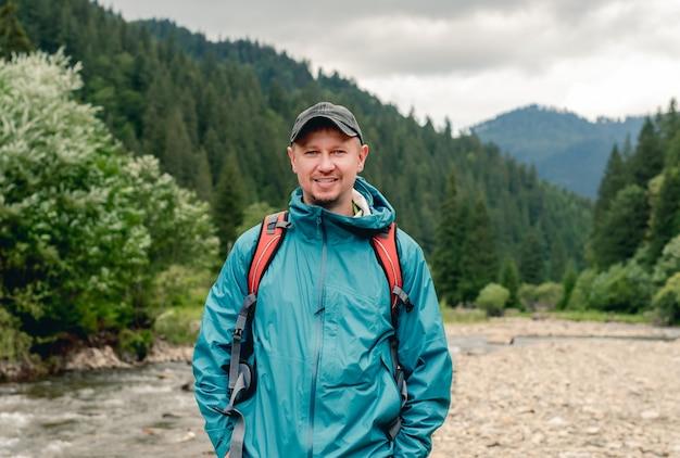 Jovem turista sorridente com uma mochila em pé na superfície da montanha do rio