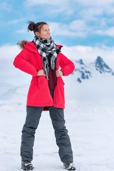 Jovem turista vestida com casaco à prova de vento de inverno vermelho, calça esporte cinza escuro e botas de trekking.
