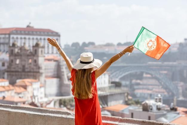 Jovem turista vestida de vermelho em pé atrás com a bandeira portuguesa no fundo da cidade velha, viajando pela cidade do porto, portugal