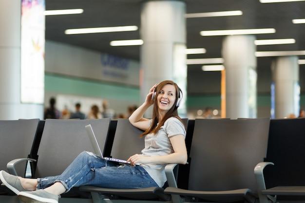 Jovem turista viajante rindo com fones de ouvido, ouvindo música trabalhando em um laptop, espere no saguão do aeroporto internacional