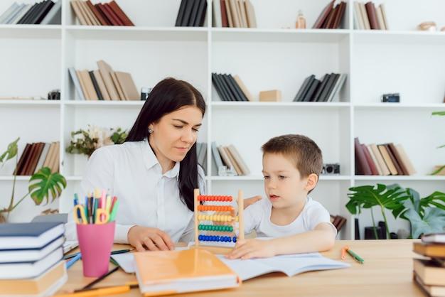 Jovem tutora ajudando o menino do ensino fundamental com a lição de casa durante uma aula individual em casa