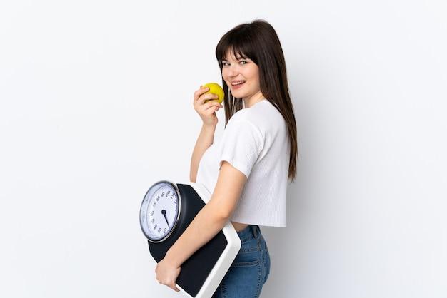 Jovem ucraniana isolada na parede branca com uma balança e uma maçã
