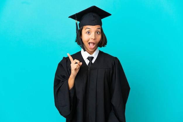Jovem universitária com um fundo azul isolado com a intenção de descobrir a solução enquanto levanta um dedo