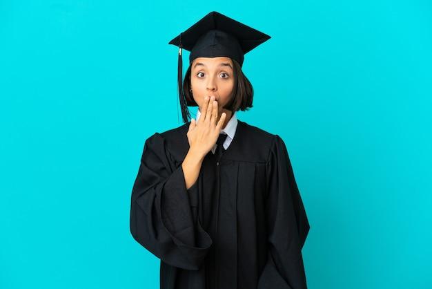 Jovem universitária sobre fundo azul isolado, cobrindo a boca com a mão