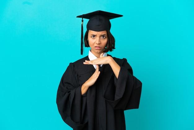 Jovem universitária sobre fundo azul isolado fazendo gesto de pausa