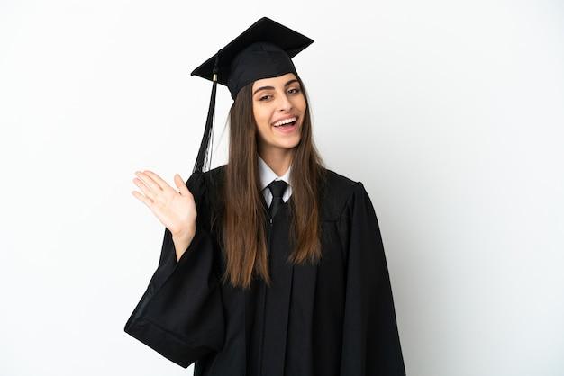 Jovem universitário isolado no fundo branco, saudando com uma mão com uma expressão feliz