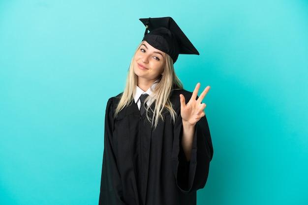 Jovem universitário sobre fundo azul isolado feliz e contando três com os dedos