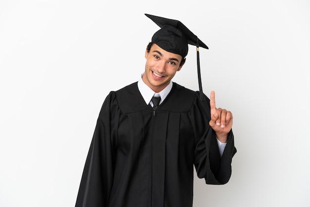 Jovem universitário sobre fundo branco isolado, mostrando e levantando um dedo em sinal dos melhores