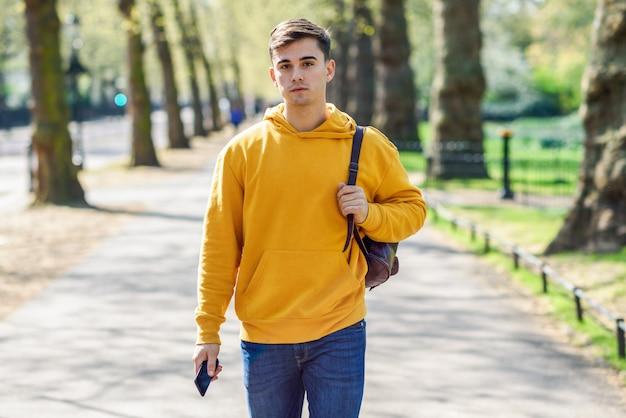 Jovem urbano usando smartphone andando na rua em um parque urbano em londres.