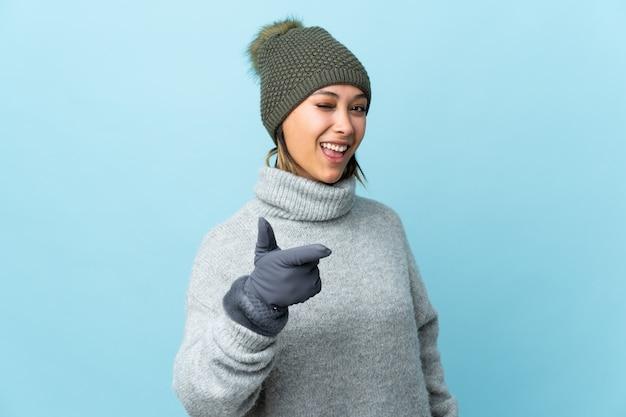 Jovem uruguaia com chapéu de inverno isolado na parede azul aponta o dedo para você