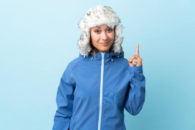 Jovem uruguaia com chapéu de inverno isolado na parede azul apontando com o dedo indicador uma ótima idéia
