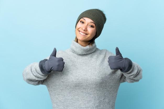 Jovem uruguaia com chapéu de inverno isolado na parede azul, dando um polegar para cima gesto