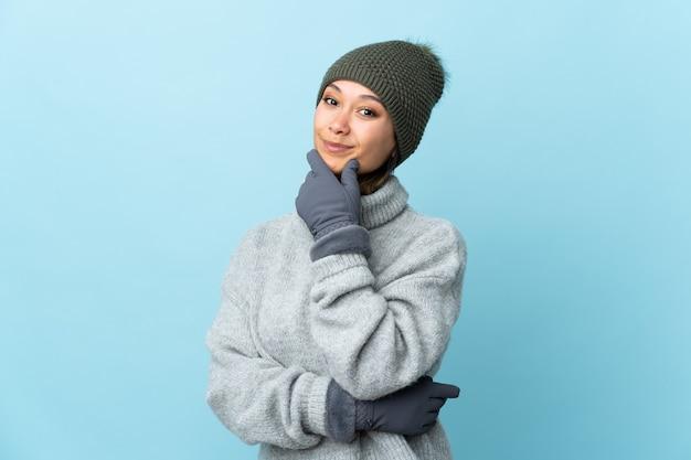 Jovem uruguaia com chapéu de inverno na parede azul rindo
