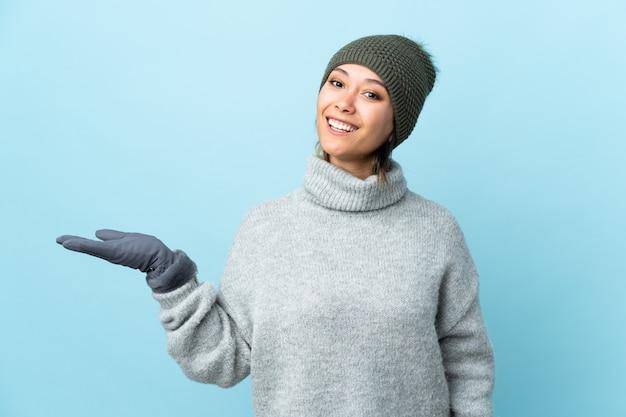 Jovem uruguaia com chapéu de inverno na parede azul segurando copyspace imaginário na palma da mão