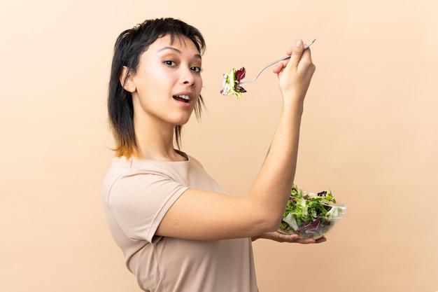 Jovem uruguaia com salada sobre parede isolada