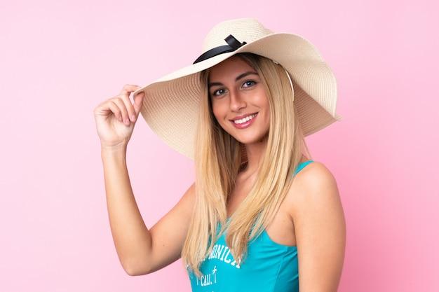Jovem uruguaia loira em traje de banho nas férias de verão sobre parede rosa isolada