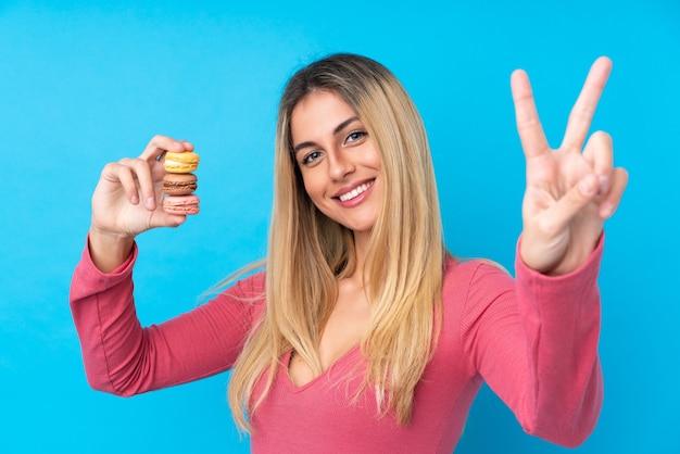 Jovem uruguaia segurando macarons franceses coloridos e mostrando sinal de vitória