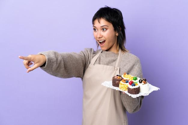 Jovem uruguaia segurando muitos mini bolos diferentes na parede roxa, apontando para fora