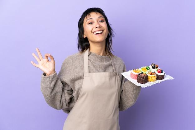 Jovem uruguaia segurando muitos mini bolos diferentes na parede roxa, mostrando um sinal de ok com os dedos