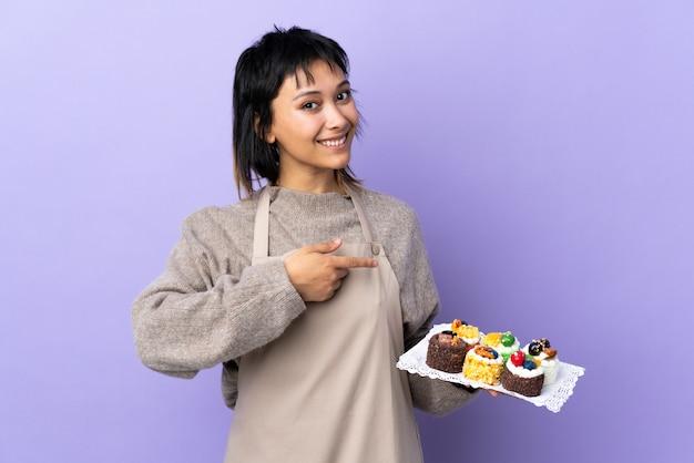 Jovem uruguaia segurando muitos mini bolos diferentes sobre parede roxa isolada, apontando o dedo para o lado